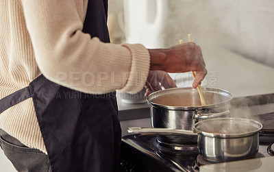 Buy stock photo Cropped shot of an unrecognizable man cooking on his stove in the kitchen at home