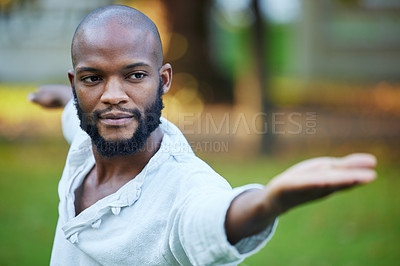 Buy stock photo Cropped shot of a handsome young man practicing yoga outside in the park