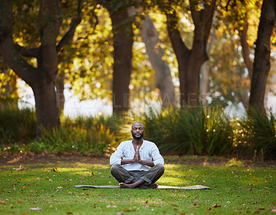 Buy stock photo Full length shot of a handsome young man meditating while practicing yoga outside at the park