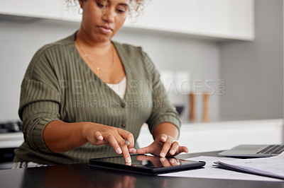 Buy stock photo Shot of a woman using a digital tablet and going through paperwork at home