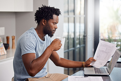 Buy stock photo Shot of a man going through some paperwork and looking worried at home while having coffee