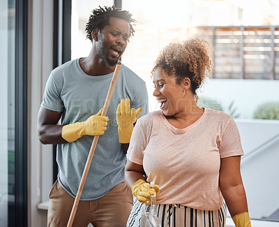 Buy stock photo Shot of a young couple singing while cleaning at home