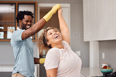 Buy stock photo Shot of a young couple dancing while cleaning at home