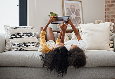 Buy stock photo Shot of two sisters using a digital tablet at home