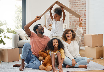 Buy stock photo Shot of a young family holding up a cardboard box to form a roof at home