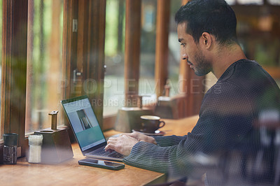 Buy stock photo Shot of a man using his laptop while sitting in a cafe