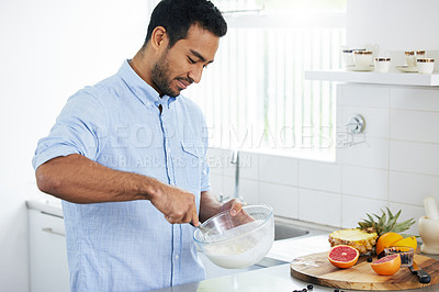 Buy stock photo Shot of a man making himself a smoothie at home