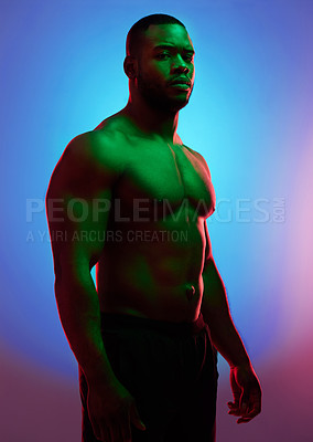 Buy stock photo Studio shot of a man posing shirtless against a neon background