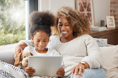 Buy stock photo Shot of a young mother using a digital tablet with her daughter at home