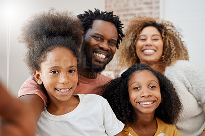 Buy stock photo Shot of a young family taking a selfie at home