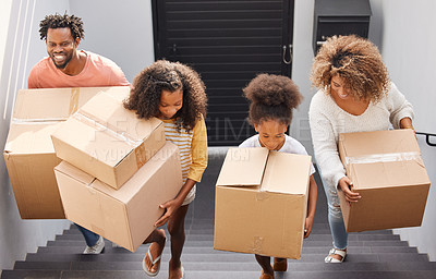 Buy stock photo Shot of a family carrying boxes into their new home