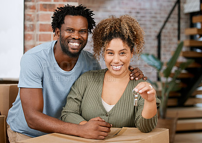 Buy stock photo Shot of a young couple showing keys to their new home