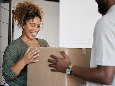Buy stock photo Shot of a young woman receiving a box from a deliveryman at home