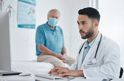 Buy stock photo Shot of a young doctor using computer in an office
