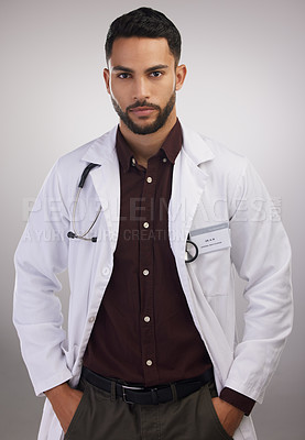 Buy stock photo Shot of a handsome young doctor standing alone in the studio