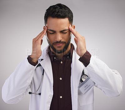 Buy stock photo Shot of a handsome young doctor standing alone in the studio and suffering from a headache