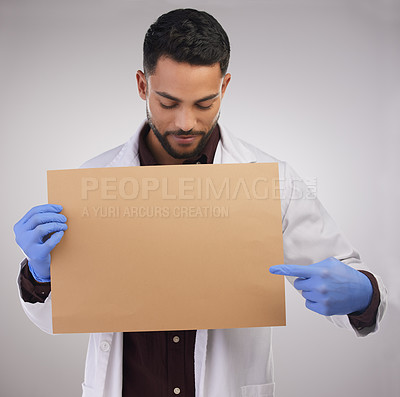 Buy stock photo Shot of a handsome young doctor standing alone in the studio and pointing at a poster