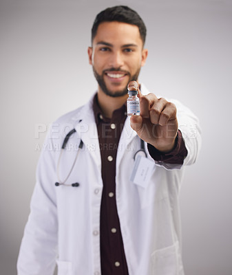 Buy stock photo Shot of a handsome young doctor standing alone in the studio and holding a vial of the Covid vaccine