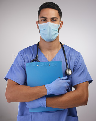 Buy stock photo Shot of a handsome young nurse standing alone in the studio and holding a clipboard while wearing a face mask