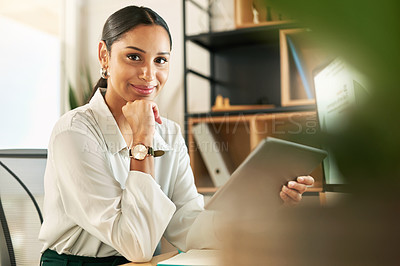 Buy stock photo Shot of a young businesswoman using her digital tablet at her desk