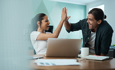 Buy stock photo Shot of a young couple doing paperwork while using a laptop at home
