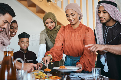 Buy stock photo Shot of a muslim family dishing lunch for themselves
