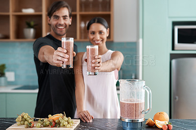 Buy stock photo Cropped portrait of an affectionate young couple making smoothies in their kitchen at home