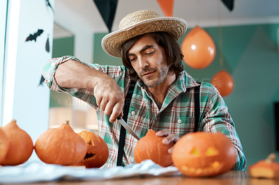 Buy stock photo Shot of a young man carving a pumpkin at home