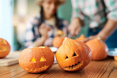 Buy stock photo Shot of a young couple carving pumpkins at home