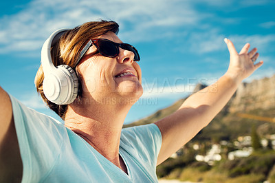 Buy stock photo Shot of a woman wearing headphones while standing outdoors