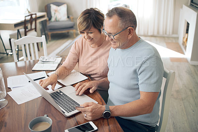 Buy stock photo Shot of a mature couple using their bank card to digitally pay their bills