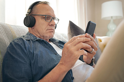 Buy stock photo Shot of a senior man using his smartphone to listen to music