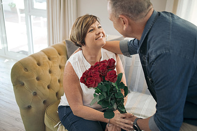 Buy stock photo Shot of a mature wife receiving a bouquet of roses from her husband