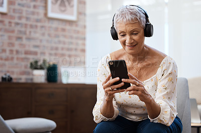 Buy stock photo Shot of a senior woman using a smartphone and headphones on the sofa at home