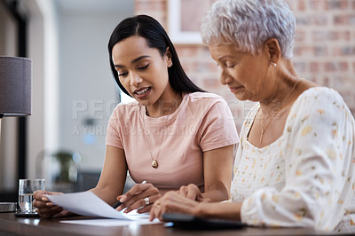 Buy stock photo Shot of a young woman going over paperwork with her elderly mother at home
