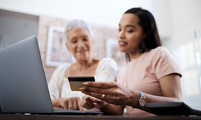 Buy stock photo Shot of a senior woman using a laptop and credit card with her daughter at home