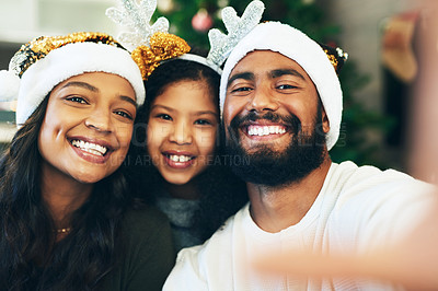 Buy stock photo Shot of a happy young family taking selfies during Christmas at home