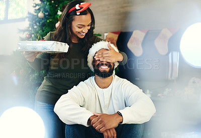 Buy stock photo Shot of a happy young couple opening presents during Christmas at home