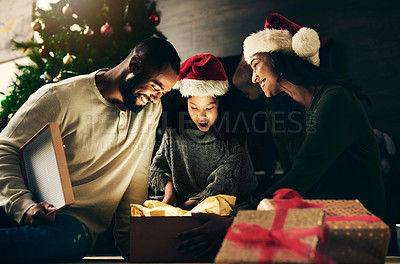 Buy stock photo Shot of a happy young family opening presents during Christmas at home