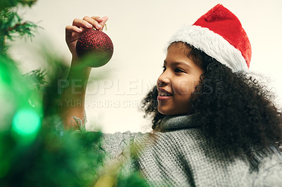 Buy stock photo Shot of a cute little girl decorating a Christmas tree at home