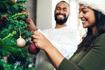 Buy stock photo Shot of a happy young couple decorating a Christmas tree at home