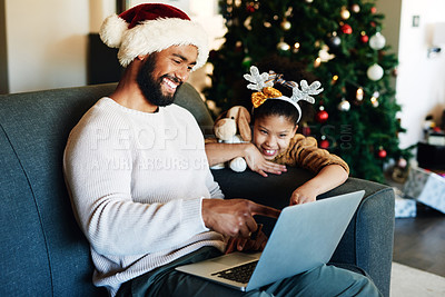 Buy stock photo Shot of a happy young father and daughter using a laptop on the sofa during Christmas at home
