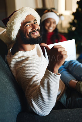 Buy stock photo Portrait of a young man showing thumbs up while using a laptop with his wife during Christmas at home