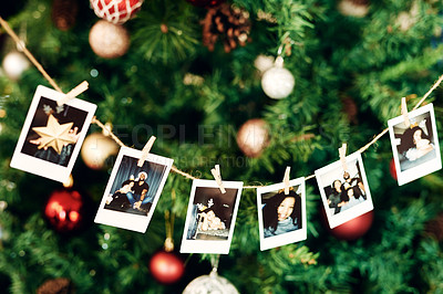 Buy stock photo Shot of a strong of family photographs hanging on a tree during Christmas at home