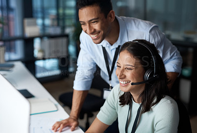 Buy stock photo Shot of a young man and woman using a computer while working in a call centre.