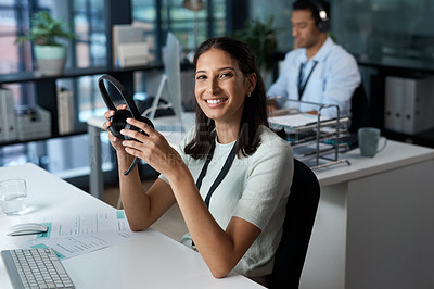 Buy stock photo Portrait of a young woman using a headset and computer in a modern office