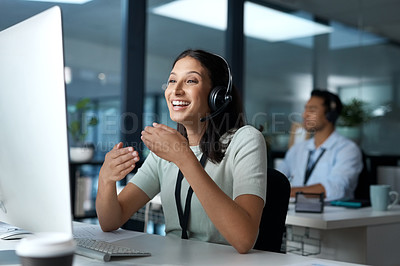 Buy stock photo Shot of a young woman using a headset and computer in a modern office