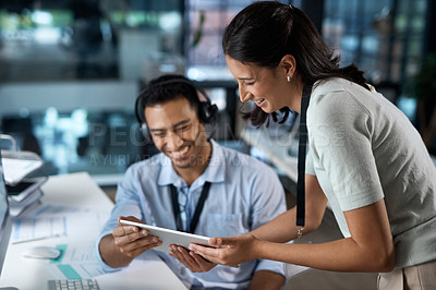 Buy stock photo Shot of a young man and woman using a digital tablet while working in a call centre