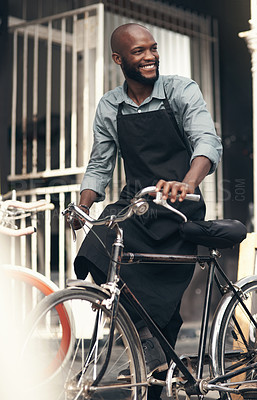 Buy stock photo Shot of a handsome young man moving a bicycle from his shop during the day