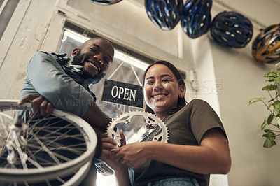 Buy stock photo Low angle shot of two young business owners standing together in their bicycle shop and holding spare parts